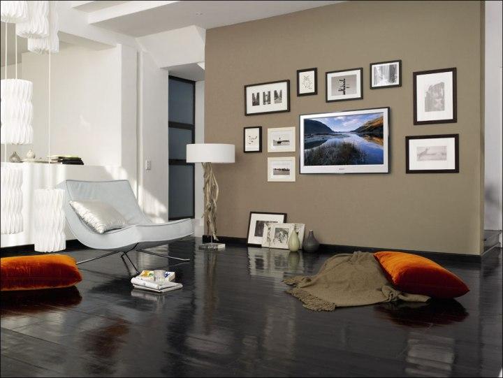 Телевизор среди картин на стене в гостиной