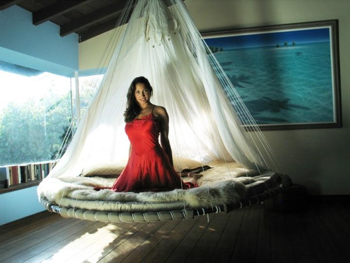Женщина сидит на круглой подвесной кровати