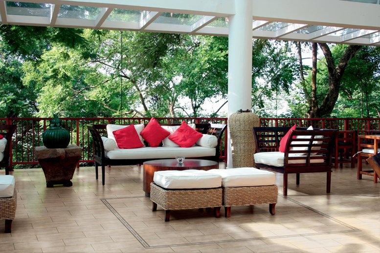 С плетенной мебелью и яркими диванными подушками